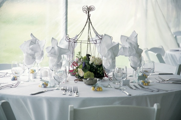 White tablecloth and chairs with caged flowers