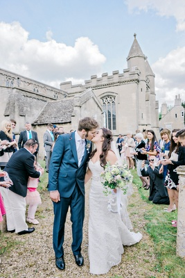 couple kiss coming st andrews church england british wedding english blue tuxedo suit ceremony exit