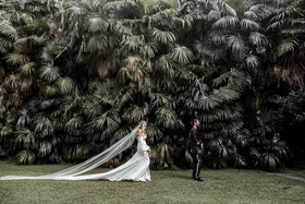 bride in daughters of simone wedding dress co owner ashley walking toward groom for first look italy