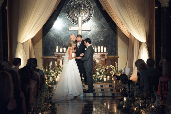Bride and groom at church decor ceremony look cross candles low flower arrangement oscar de la renta