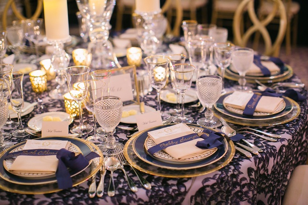 wedding reception round table pattern linen gold plates gold calligraphy on navy blue ribbon place