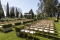 Manicured hedges and gold chairs on grass lawn