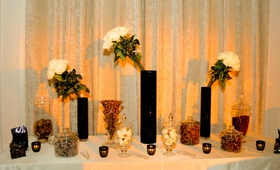Tall black vases with glass jars of candy and chocolate