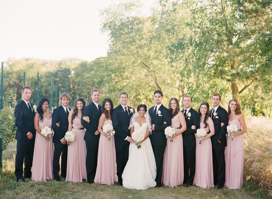 Bride and groom with groomsmen in black suits and ties and bridesmaids in pink dresses in an orchard