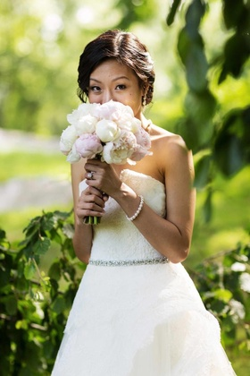 Bride in a strapless Monique Lhuillier gown holds a bouquet of pink and white peonies
