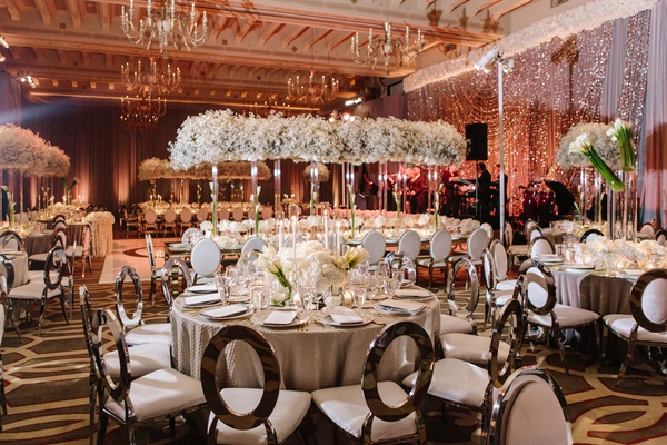 warm ambience of ballroom wedding silver round back chairs modern decor white flowers