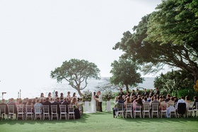 outdoor destination wedding ceremony in waimea hawaii white chairs greenery ocean backdrop trees