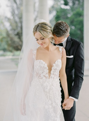 wedding portrait bride in berta wedding dress illusion plunging neckline veil updo groom bow tie tux