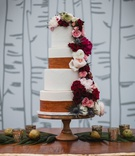 wedding cake with wood trim design and fresh flowers fall colors on wood vintage table birch branch