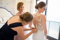 maid of honor buttoning back of wedding dress, bride in pronovias atelier