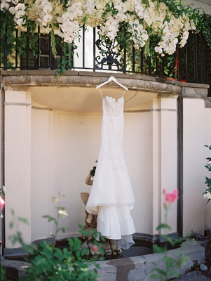 a brides trumpet gown with scalloped neckline suspended from balcony over pond
