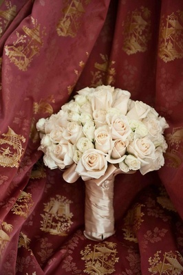 White and cream roses tied in blush ribbon