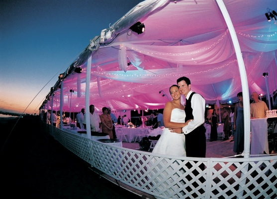 White tent in front of sunset with pink and purple lighting