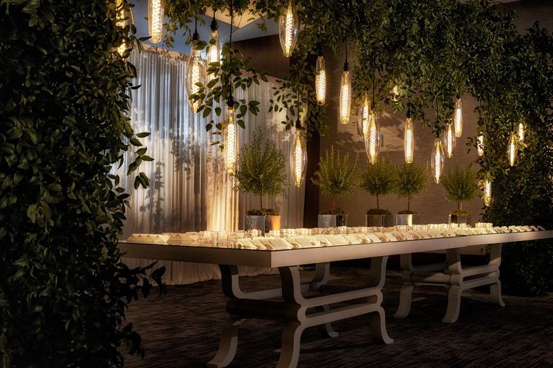 wedding escort card table cocktail hour edison bulb lights trees greenery custom table design