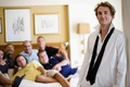 Man with loose tie with friends in hotel room