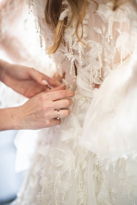 bride in marchesa wedding dress beads appliques designer being put on by mother