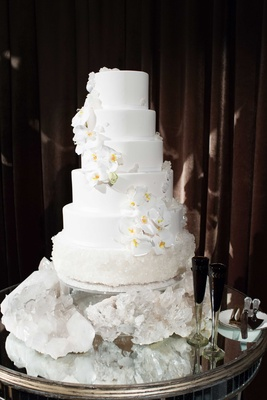 White wedding cake with fresh orchids and geode crystal bottom layer and cake table black champagne