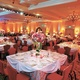 ballroom with white tables, red chairs and pink flowers