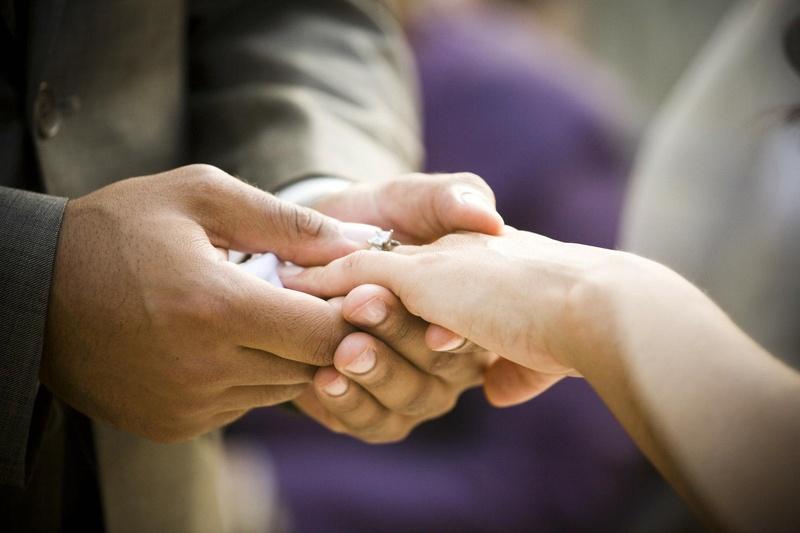 Groom puts wedding ring on bride's ring finger