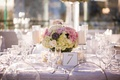 Ghost chairs around wedding reception table with low centerpiece succulent, hydrangea, rose, dahlia