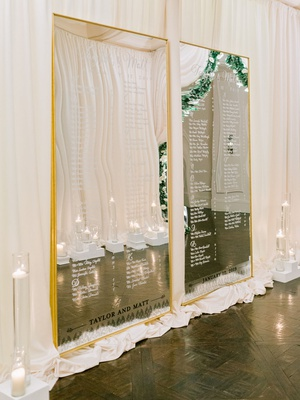 wedding reception entrance seating chart mirror gold frame white script candles hallway