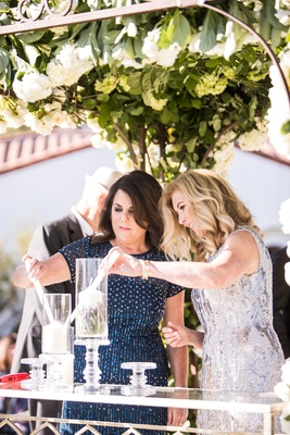 Mother of groom and mother of bride lighting candles in hurricane vases on crystal stands ceremony
