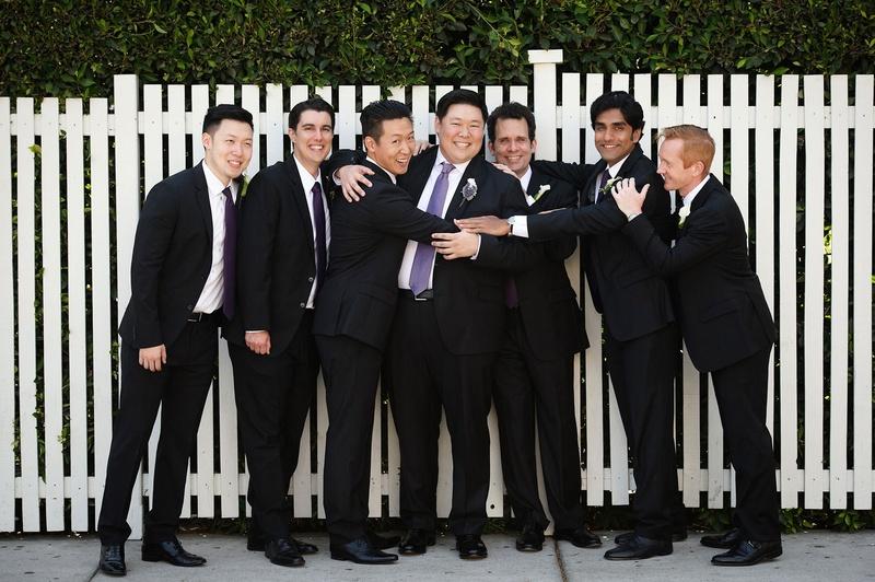 Groom and groomsmen smile and hug before wedding ceremony purple ties light purple dark purple