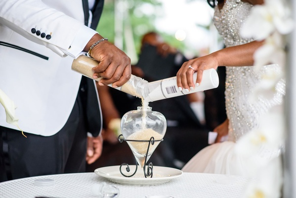 African American bride and groom pouring white and tan sand into container wedding ceremony