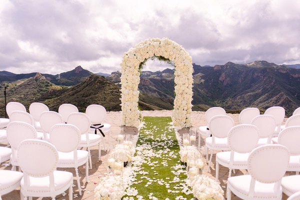 malibu rocky oaks ceremony, white chairs, ivory floral arch