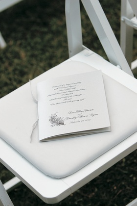 White wedding program with a silver ribbon and script font
