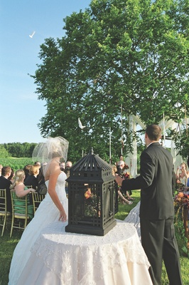 Bride and groom open cage filled with doves