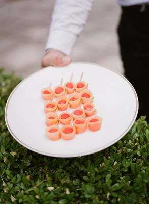 Wedding reception hors d'oeuvres appetizer held over green hedge by server