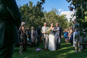 bride walking down grass aisle with dad and stepdad in grey suits guests standing
