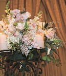 Pink and white flowers in the center of a candelabra with pink candles