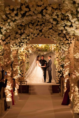 Bride and groom at ceremony altar through tunnel of flowers