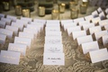 White wedding escort card with gold foil calligraphy table with lace linens