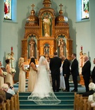 Bride and groom with wedding party on steps of altar