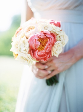 Bridesmaid holding bouquet of white roses and hot pink peonies