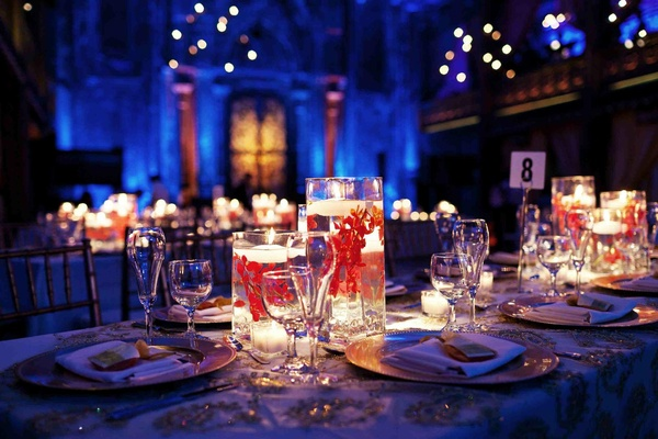 Blue reception lighting and red flower in floating candle centerpiece