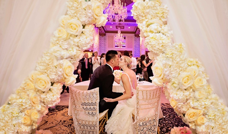 rob refsnyder of new york yankees kisses bride at sweetheart table with dramatic flower curtain