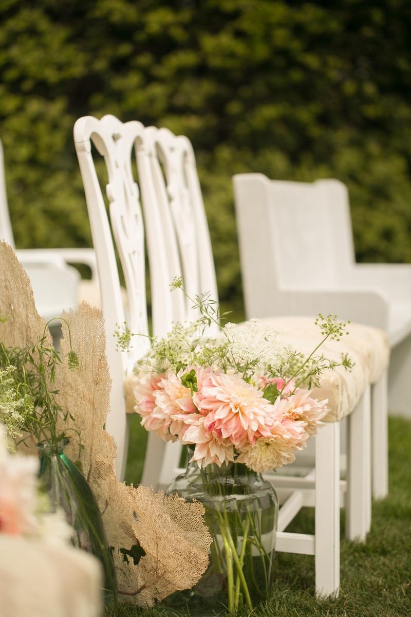 Antique white ceremony chairs with dahlia arrangement