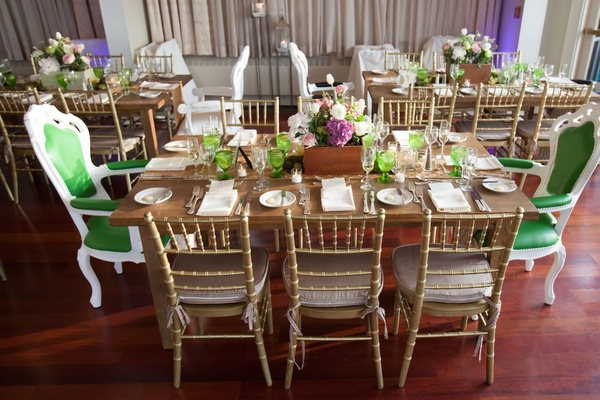 Wedding reception wood table with green glassware, high-back white and green chairs, and gold chairs