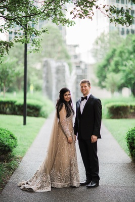 bride in elan, groom in armani pose in park in pittsburgh