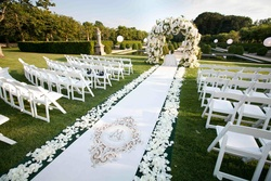Garden wedding ceremony with white monogrammed aisle runner and white floral arch
