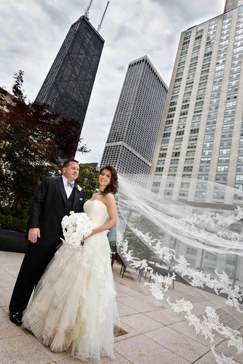 bride and groom stand in chicago bride's vera wang veil flowing in the wind white orchid bouquet