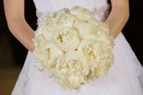 Bride in white Vera Wang wedding dress holding ivory bouquet of all white peony flowers