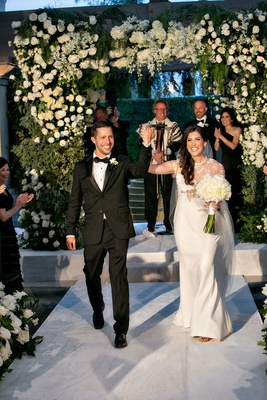 Bride in j mendel wedding dress groom in tuxedo chuppah white flowers celebrate being married