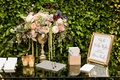 Escort card table with guest book address book sign gold vase with flowers