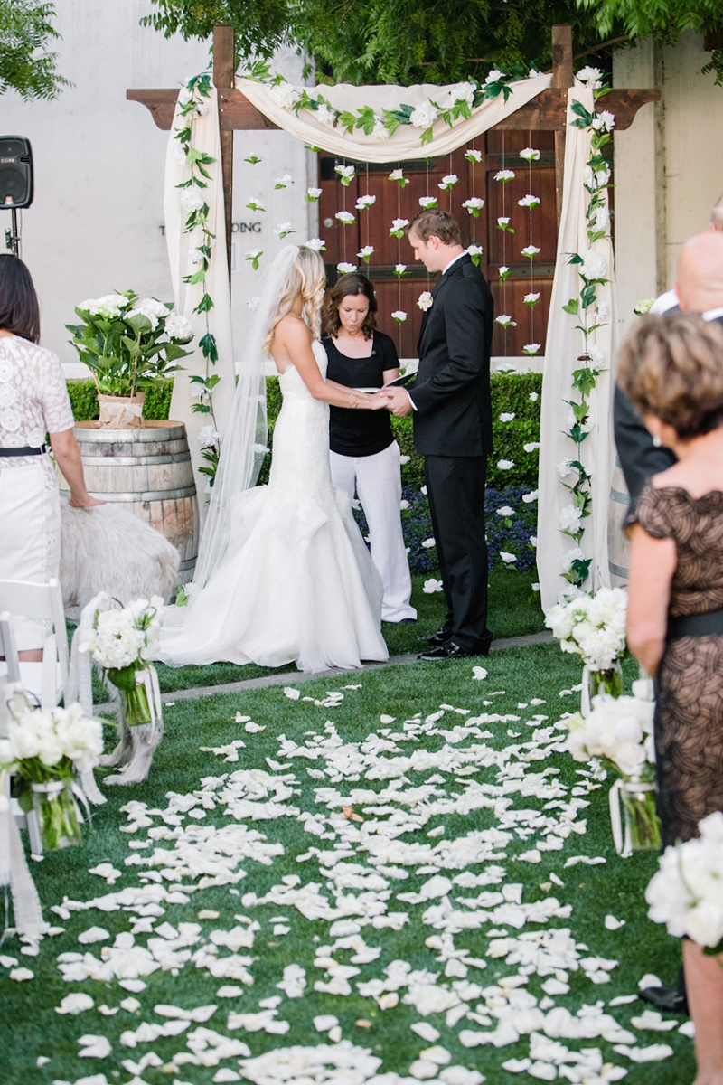 Bride in a strapless Hayley Paige dress and veil with groom at outdoor ceremony with white flowers