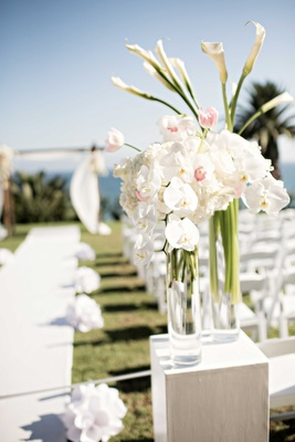 glass vases top of aisle white pink flowers on stands long and short outdoor ocean side wedding